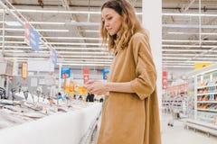 La giovane donna di affari con una compressa seleziona il pesce in un supermercato Immagine Stock Libera da Diritti
