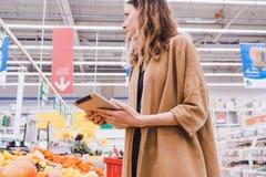La giovane donna di affari con una compressa in sue mani compra l'alimento in un supermercato immagine stock