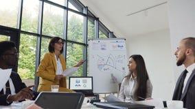 La giovane donna di affari conduce la presentazione facendo uso della lavagna su cui mostra i grafici comprare e la società di ve stock footage