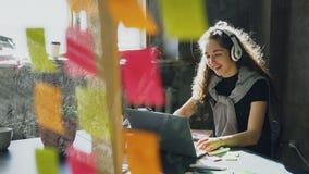 La giovane donna di affari creativa sta ascoltando musica in cuffie che ballano e che cantano mentre lavorava allo scrittorio con archivi video