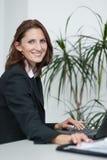 La giovane donna di affari di attractice utilizza il suo computer portatile Fotografie Stock Libere da Diritti