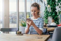 La giovane donna di affari in maglietta a strisce sta sedendosi alla tavola in caffè vicino alla finestra e sta utilizzando lo sm Fotografie Stock