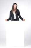 La giovane donna di affari riguarda il suo ritardo di manifesto in bianco. Fotografia Stock