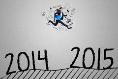 La giovane donna di affari salta sopra i numeri 2014 - 2015 Fotografia Stock Libera da Diritti
