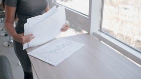 La giovane donna di affari sexy sta analizzando i documenti che stanno nell'interno dell'ufficio video d archivio