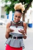 La giovane donna di affari sorride mentre esamina la sua compressa Immagine Stock
