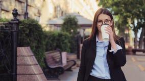 La giovane donna di affari sta camminando sulla via e beve il caffè e smartphone usando all'intervallo di pranzo video d archivio