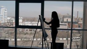 La giovane donna di affari sta scrivendo sul cartone, stante all'ufficio moderno stock footage