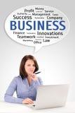 La giovane donna di affari sta sedendosi davanti ad un computer portatile nell'ambito dello speec Fotografia Stock