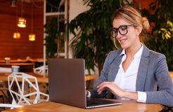 La giovane donna di affari utilizza il computer portatile in caffè Stile di vita e concetto di affari immagini stock libere da diritti