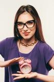 La giovane donna di affari in vetri con la sveglia Immagine Stock