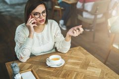 La giovane donna di affari in vetri e maglione bianco sta sedendosi in caffè alla tavola di legno e sta parlando sul telefono cel Immagine Stock