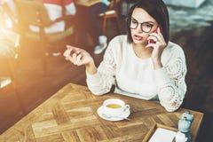 La giovane donna di affari in vetri e maglione bianco sta sedendosi in caffè alla tavola di legno e sta parlando sul telefono cel Fotografia Stock Libera da Diritti