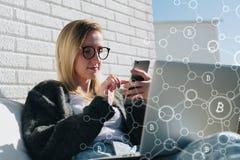 La giovane donna di affari in vetri si siede al computer portatile ed utilizza lo smartphone In infographics della priorità alta, Immagine Stock Libera da Diritti