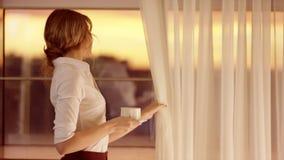 La giovane donna di bellezza apre le tende sulla grande finestra e guarda da  stock footage