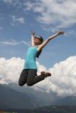 La giovane donna di felicità sta saltando contro cielo blu Giorno pieno di sole di estate Fotografie Stock Libere da Diritti