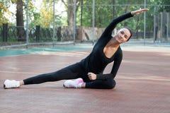 La giovane donna di forma fisica allunga durante l'allenamento di addestramento sul playgro Fotografie Stock Libere da Diritti