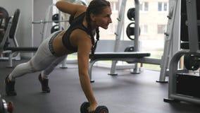 La giovane donna di forma fisica che fa la testa di legno rema alla palestra del crossfit Ragazza allegra che si esercita - peso  Fotografia Stock Libera da Diritti