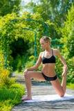 La giovane donna di forma fisica che fa la forma fisica si esercita nel parco su verde Fotografia Stock