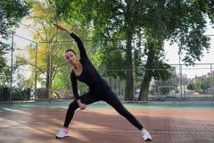La giovane donna di forma fisica fa l'allungamento degli esercizi durante il treno di sport Fotografia Stock Libera da Diritti
