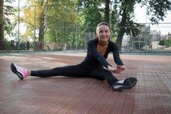 La giovane donna di forma fisica fa l'allungamento degli esercizi durante il treno di sport Immagini Stock