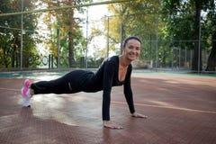 La giovane donna di forma fisica fa l'allungamento degli esercizi durante l'addestramento sopra Fotografie Stock