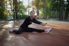 La giovane donna di forma fisica fa l'allungamento degli esercizi durante l'allenamento sopra Immagini Stock