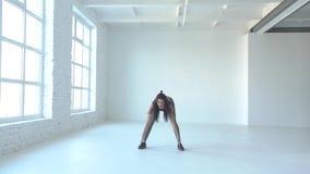 La giovane donna di forma fisica sta facendo gli edifici occupati e sta sollevando le mani su Scaldarsi gli esercizi Posizione de stock footage