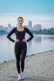La giovane donna di forma fisica sta sul pilastro all'alba di mattina Fotografia Stock Libera da Diritti