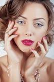 La giovane donna di lusso di bellezza con gioielli, gli anelli, chiodi si chiude su su bianco Fotografia Stock