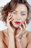 La giovane donna di lusso di bellezza con gioielli, gli anelli, chiodi si chiude su su bianco Fotografie Stock