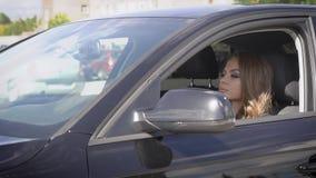 La giovane donna di lusso sta conducendo l'automobile nera sulla via della città nel giorno soleggiato dell'estate, vista del pri video d archivio