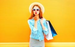La giovane donna di modo invia a tenute di un bacio dell'aria i sacchetti della spesa in cappello di paglia Immagini Stock