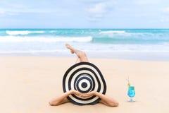 La giovane donna di modo si rilassa sulla spiaggia Stile di vita felice dell'isola immagine stock