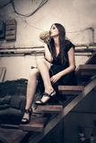 La giovane donna di modo in vestito nero nel vecchio studio dell'artista si siede sulla s immagine stock libera da diritti