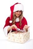 La giovane donna di natale sta aprendo i presente di natale Immagine Stock