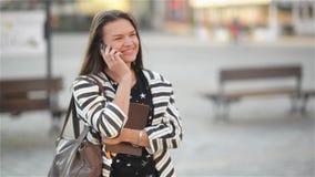 La giovane donna di risata emozionante felice che parla sul telefono cellulare e sulla ragazza ondeggia la sua mano alla via, fon video d archivio