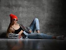 La giovane donna di sport dopo il dito di seduta del punto di esercizio di allenamento in argento dimagrisce il cappello rosso de immagine stock libera da diritti