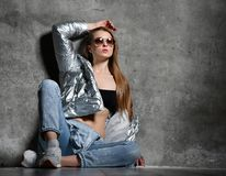La giovane donna di sport dopo l'esercizio di allenamento che si siede sotto la neve in argento dimagrisce le blue jeans del rive fotografie stock