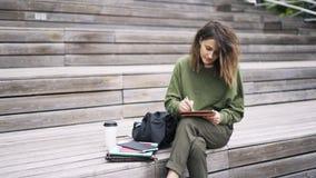 La giovane donna in disegno verde alla sua compressa sulle scale, inclina giù stock footage