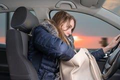 La giovane donna ? distratta mentre conduce l'automobile fotografia stock
