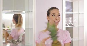 La giovane donna divertente gioca con l'ananas sulla cucina stock footage