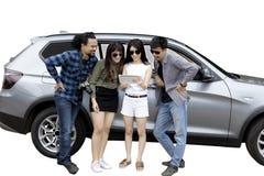 La giovane donna e gli amici si appoggiano un'automobile Fotografia Stock