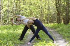 La giovane donna e l'uomo caucasici attraenti adulti delle coppie che fanno gli sport si esercita all'aperto nel parco Fotografie Stock Libere da Diritti