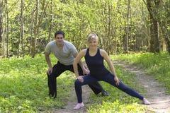 La giovane donna e l'uomo caucasici attraenti adulti delle coppie che fanno gli sport si esercita all'aperto nel parco Immagini Stock