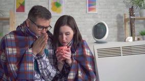 La giovane donna e l'uomo congelati si sono avvolti in una coperta nel salone sono riscaldati accanto alle stufe elettriche si ch video d archivio