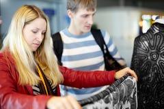 La giovane donna e l'uomo considerano il tessuto variopinto Fotografia Stock Libera da Diritti