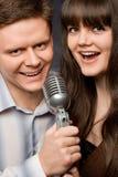 La giovane donna e l'uomo sorridente cantano in microfono Fotografia Stock