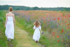 La giovane donna e la neonata in vestiti bianchi vanno sul prato i dell'estate Immagine Stock