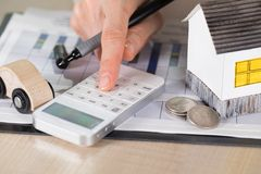 La giovane donna effettua alcuni calcoli Piccola casa di carta, monete, c fotografie stock